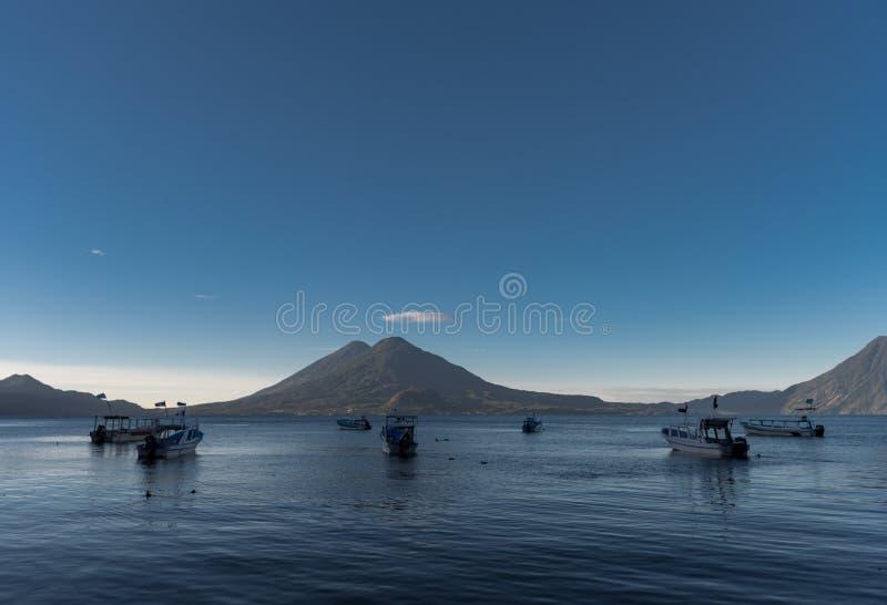 Boote im Wasser und Atitlan See in Guatemala Lange Berührung Vulkan im Hintergrund Mann, der in seinem Bett schläft lizenzfreie stockbilder
