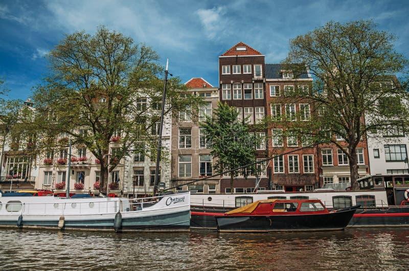Boote machten an der Seite Kanals des von Bäumen gesäumt, der Gebäude und des sonnigen blauen Himmels in Amsterdam fest lizenzfreie stockfotografie