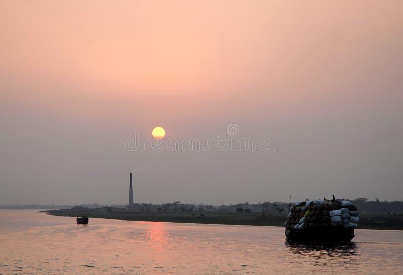 Boote am Rupsa Fluss bei Khulna in Bangladesch bei Sonnenuntergang lizenzfreie stockfotos