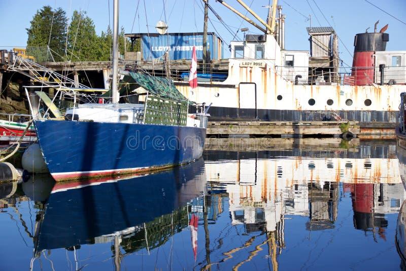 Boote in Tofino, Kanada, reflektiert im Hafen wässert stockfotografie