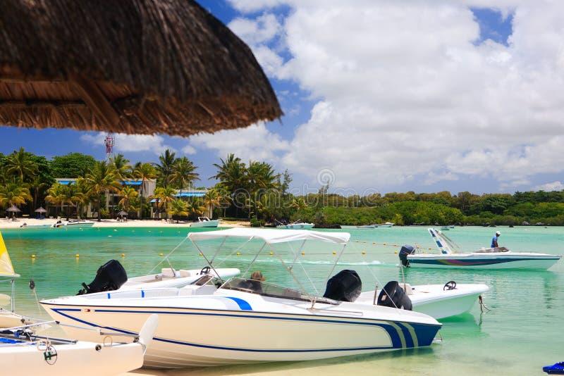 Boote am tropischen Strandurlaubsort stockfoto