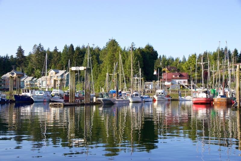 Boote und Bäume in Tofino, Kanada, reflektiert im Hafen wässert lizenzfreies stockfoto