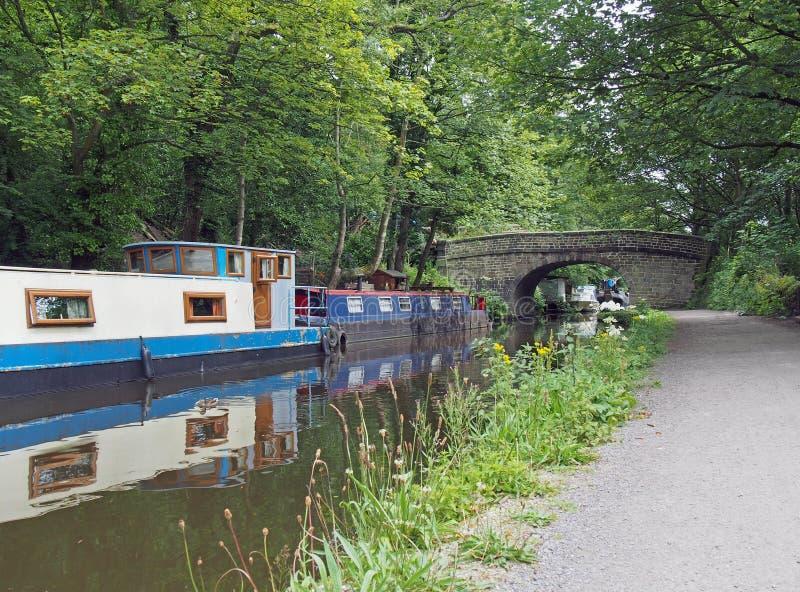 Boote und Schleppkähne, die auf dem rochdalen Kanal in der hebdenen Brücke neben einer alten Steinbrücke, umgeben von grünem Somm lizenzfreie stockbilder
