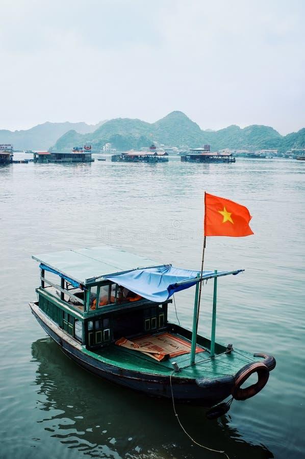 Boote und sich hin- und herbewegende Stelzenhäuser an der berühmten langen Bucht ha stockfotografie