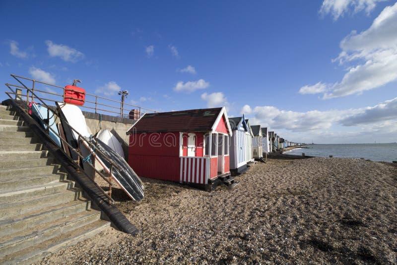 Boote und Strandhütten auf Thorpe Bay setzen, Essex, England auf den Strand stockfotos