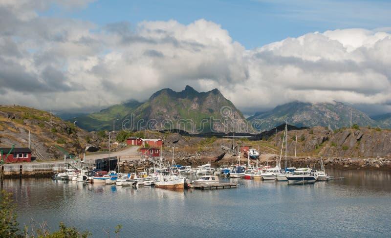 Boote und Yachten in einer Bucht auf einem Hintergrund von Bergen, Lofoten, Norwegen lizenzfreie stockfotos