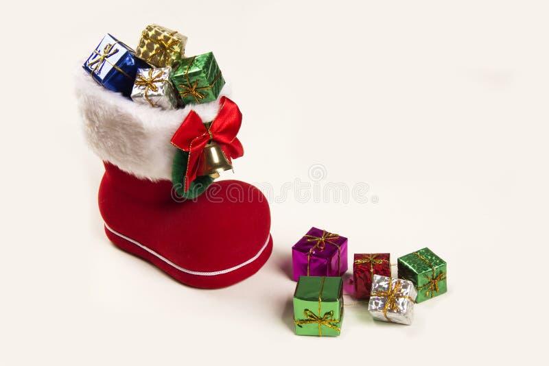 Bootie rojo de santa con los regalos de la Navidad en el fondo blanco fotografía de archivo