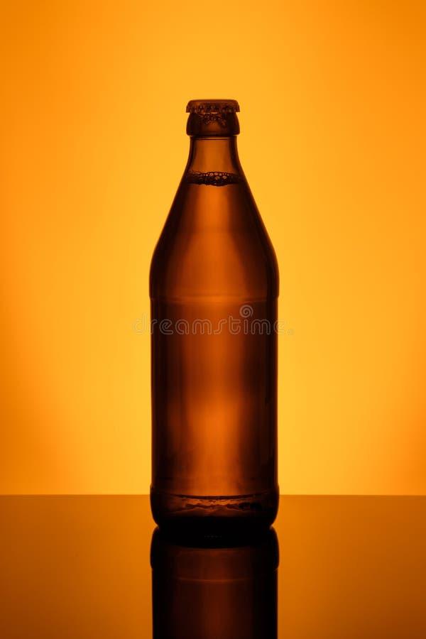 Bootle da cerveja com o tampão de coroa na parte traseira leve fotos de stock royalty free