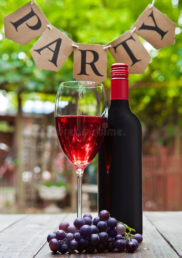 Bootle i szkło redd wino z przyjęcie listami w parku fotografia stock