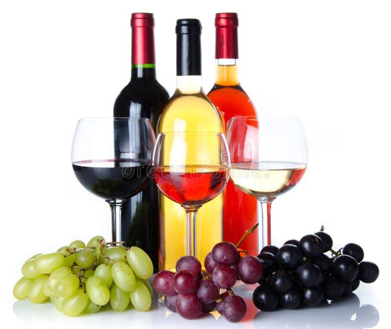 Bootles y vidrios de vino con las uvas negras, rojas y blancas fotografía de archivo libre de regalías
