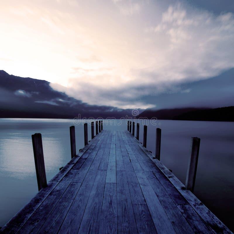 Bootpier en een kalm meer bij zonsopgang, Nieuw Zeeland stock afbeeldingen