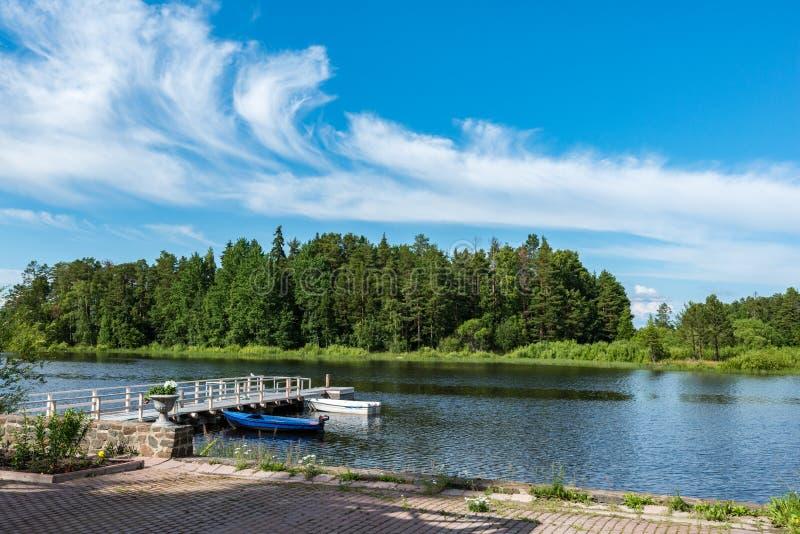 Bootpost en een mooie pijler op de kust van het meer in het midden van de weelderige bossen van het Eiland Valaam stock afbeeldingen
