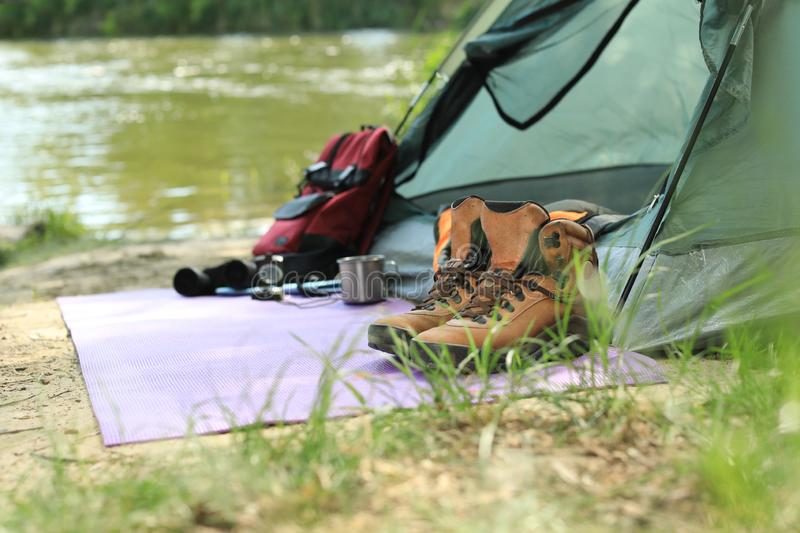 Boots and camping equipment near tent on riverbank stock photography