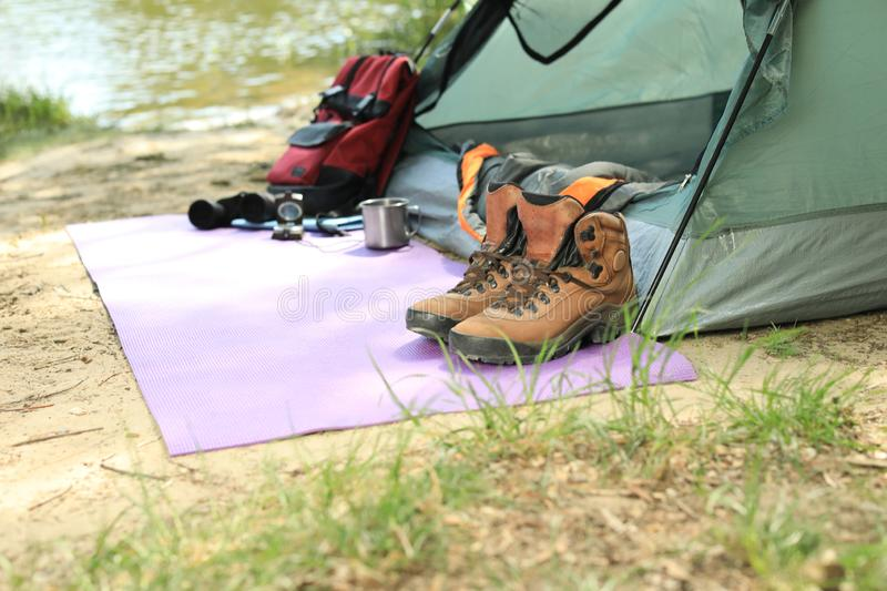 Boots and camping equipment  tent on riverbank. Space for text stock images