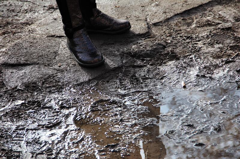 Boots of a child near a puddle. Rainy, dark days. stock photo