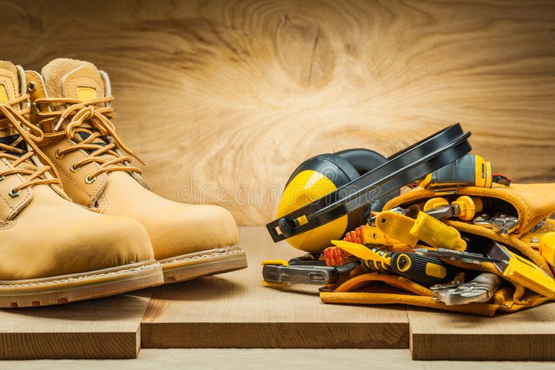 Boots and earphones on tool belt with construction tools stock image