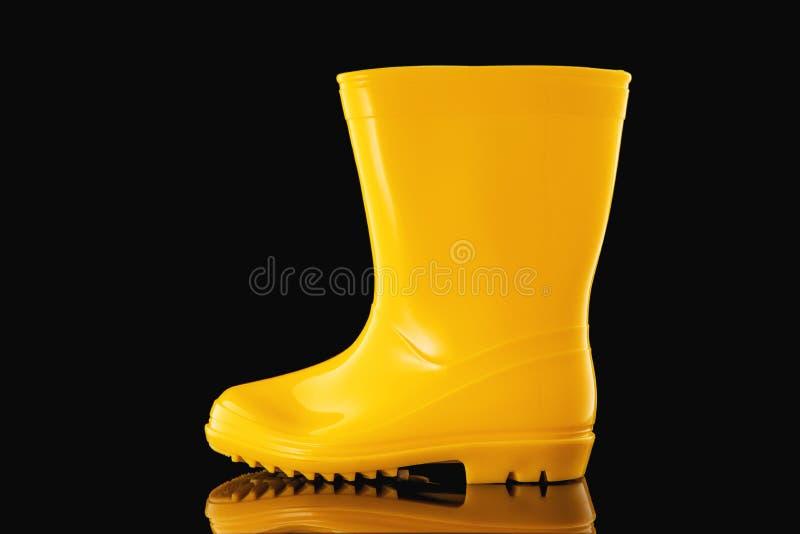 Boots in gomma gialla per bambini con fondo nero fotografie stock