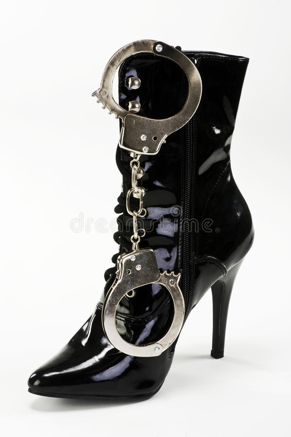 Boots and Handcuff. Leather boots and ladies handcuffs stock photos