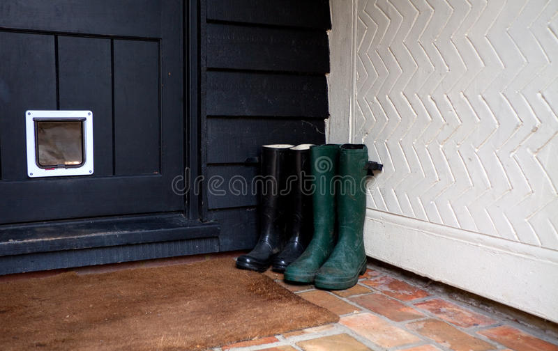 Boots by house door. Two pair of wellingtons or galoshes in a porch outside a kitchen door depicting country living stock photos