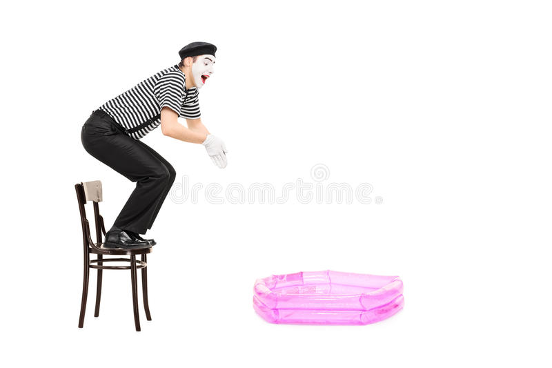 Boots kunstenaar het springen in een kleine opblaasbare pool i na stock foto