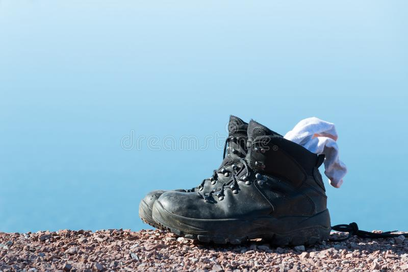 Hiking boots. Boots with lake and reflection royalty free stock image