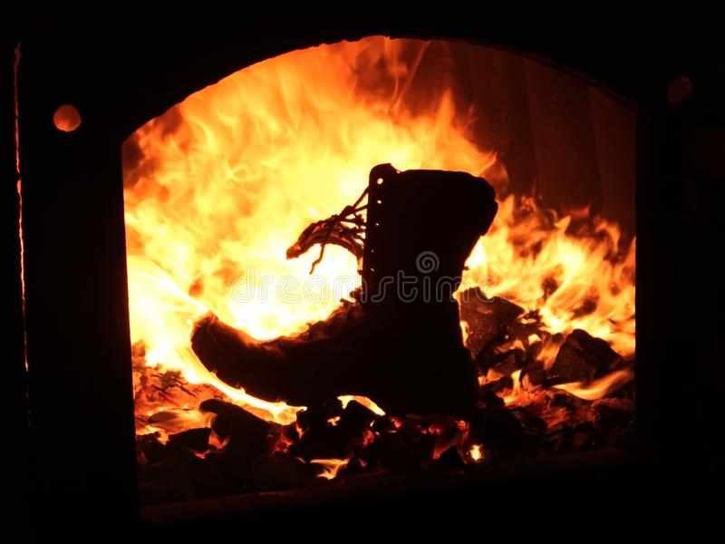 Boots military burns in the furnace of the fire of war royalty free stock photo
