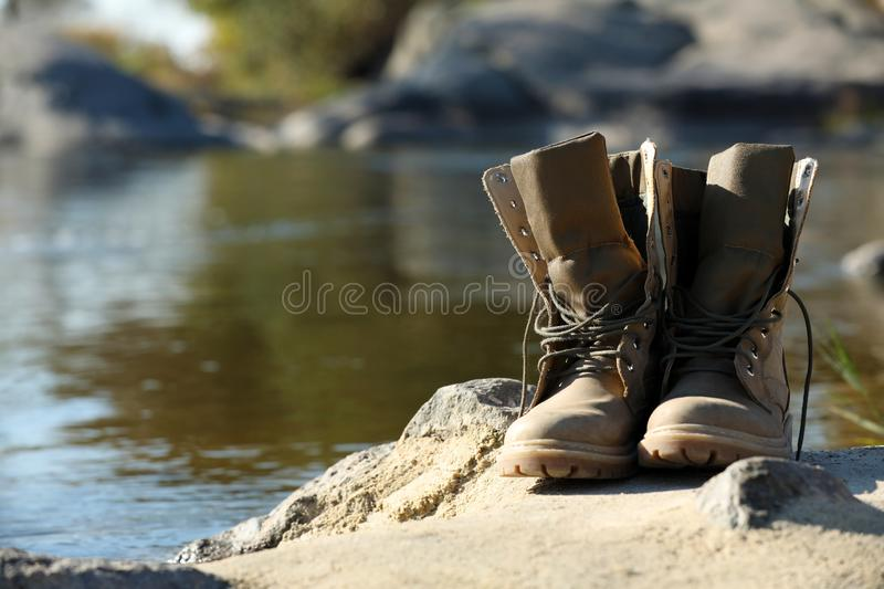 Boots on sand near pond. stock images