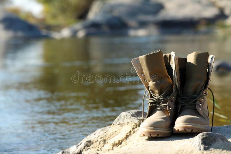 Boots on sand near pond. royalty free stock photo