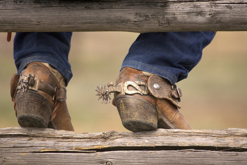 Boots and Spurs. Cowboy boots and spurs resting on a split rail fence
