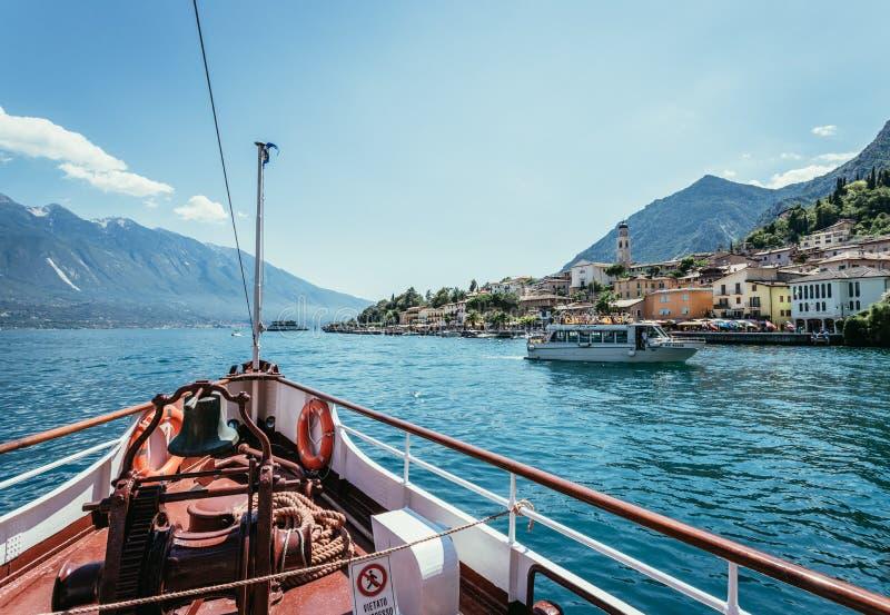 Bootsausflug: Bootsbogen, Ansicht ?ber Azurblauwasser, Dorf und Gebirgszug Lago di Garda, Italien stockfotografie