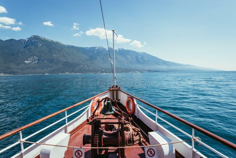 Bootsausflug: Bootsbogen, Ansicht ?ber Azurblauwasser, Dorf und Gebirgszug Lago di Garda, Italien stockbilder