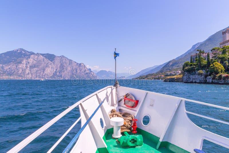Bootsausflug: Bootsbogen, Ansicht ?ber Azurblauwasser, Dorf und Gebirgszug Lago di Garda, Italien lizenzfreie stockfotografie