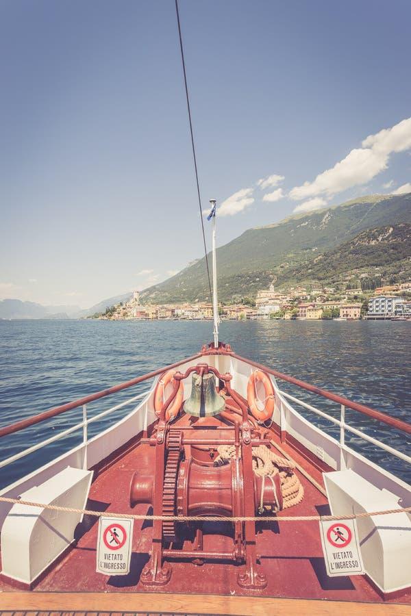 Bootsausflug: Bootsbogen, Ansicht ?ber Azurblauwasser, Dorf und Gebirgszug Lago di Garda, Italien stockfoto