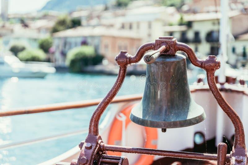 Bootsausflug: Bootsbogen mit Bootsglocke, Ansicht ?ber Azurblauwasser, Gebirgszug und kleines Dorf Lago di Garda, Italien lizenzfreies stockfoto
