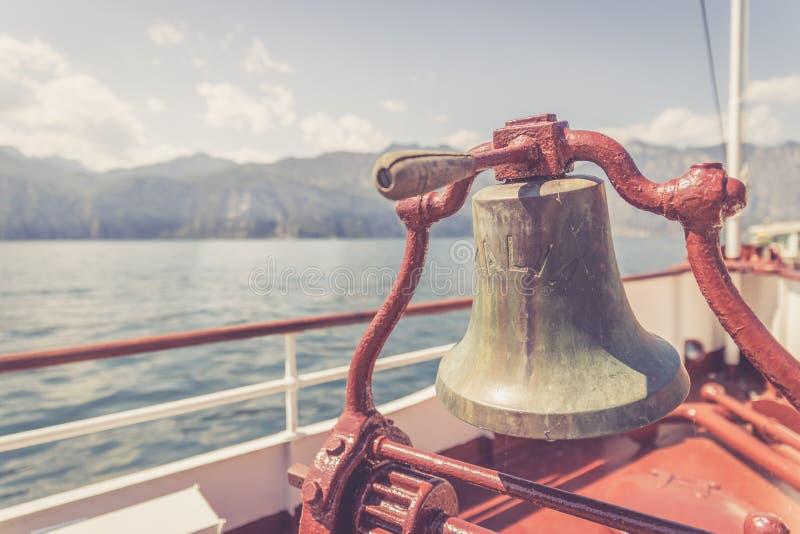 Bootsausflug: Bootsbogen mit Bootsglocke, Ansicht ?ber Azurblauwasser, Gebirgszug und kleines Dorf Lago di Garda, Italien stockfotos