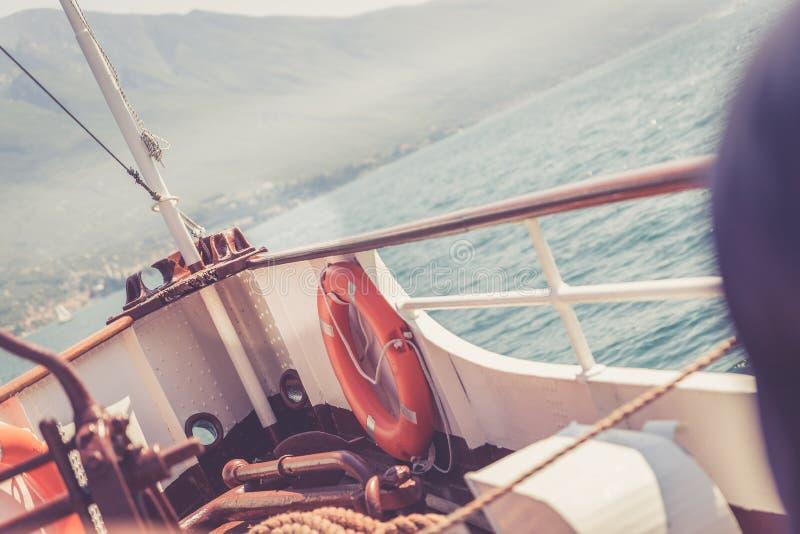 Bootsausflug: Bootsbogen mit Rettungsboje, Ansicht über Azurblauwasser und Gebirgszug Lago di Garda, Italien lizenzfreie stockfotos