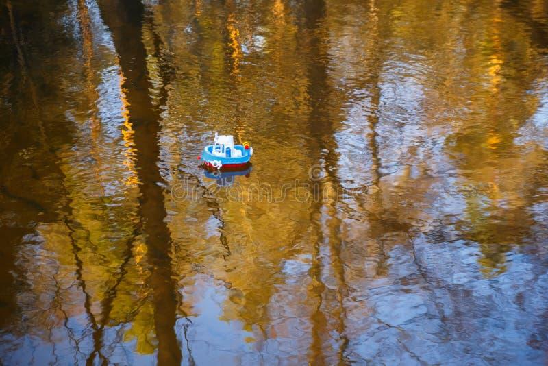 Bootsblau der Kinder geht auf das goldene Wasser stockfotografie