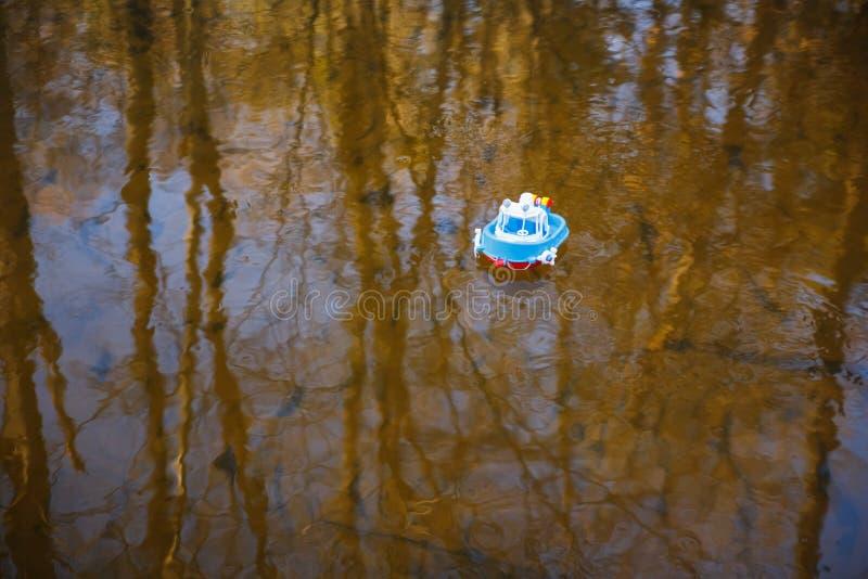 Bootsblau der Kinder geht auf das goldene Wasser stockbilder
