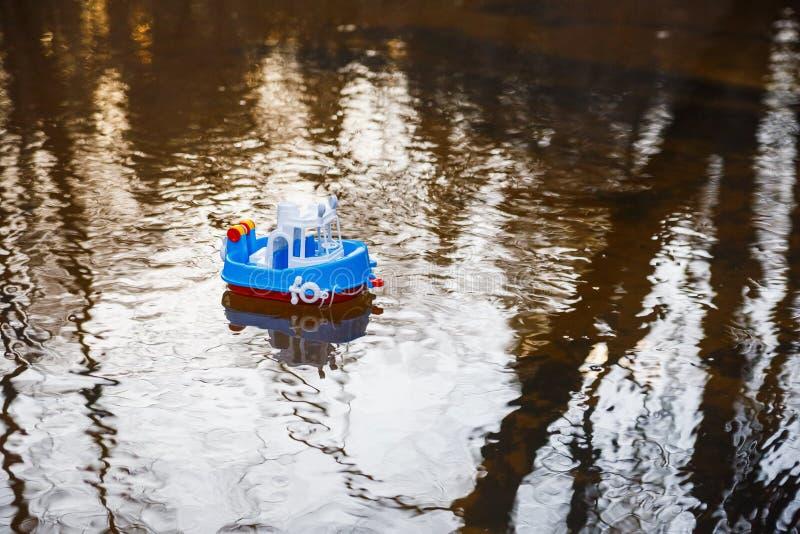 Bootsblau der Kinder geht auf das goldene Wasser lizenzfreies stockfoto