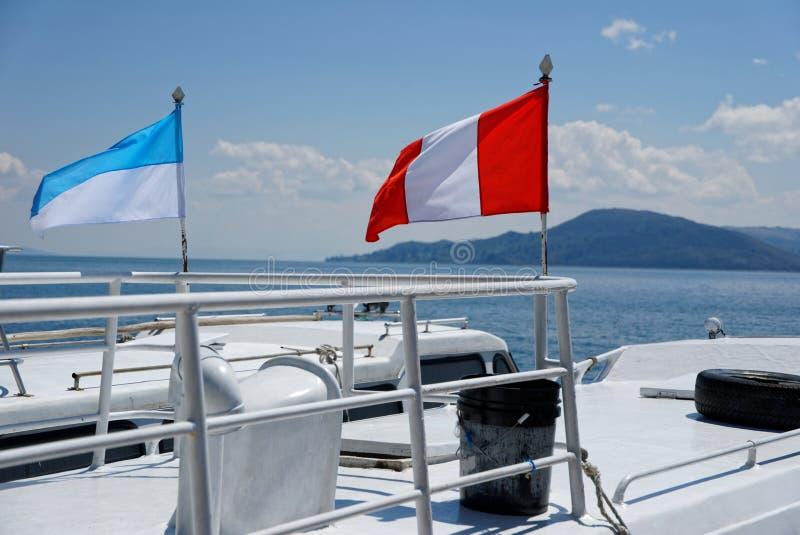 Bootsfahrt mit wellenartig bewegender Flagge stockfotografie