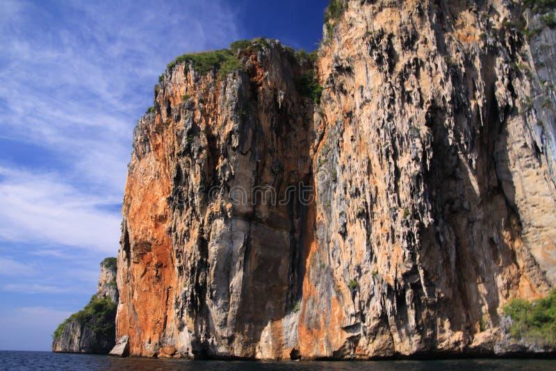 Bootsreise nach dem Küstengrundsatz von Tropeninsel Ko Phi Phi entlang der eindrucksvollen steilen roten Felsenwand, die hoch in  lizenzfreies stockbild