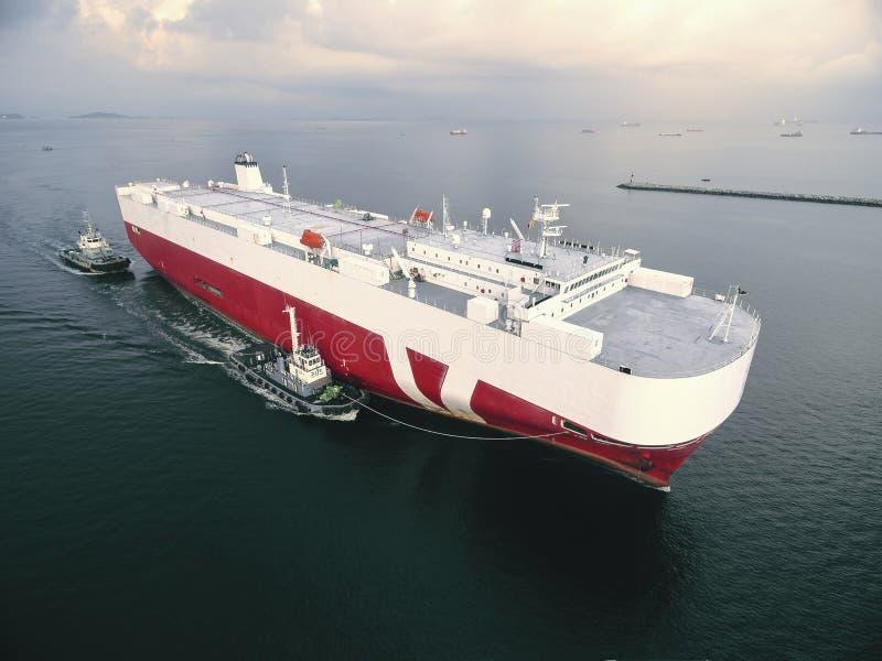 Bootsschleppen-Autotransporterschiff mit zwei Schleppern gehen anzukoppeln lizenzfreie stockbilder