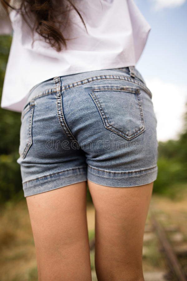 Booty girl in denim shorts in the park stock photography