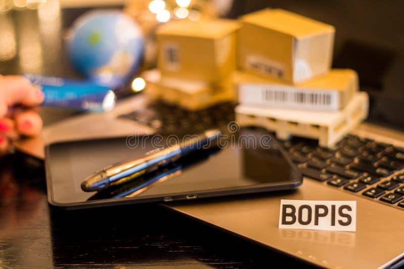 BOPIS - Recolhimento em linha da compra na loja - ainda conceito do negócio da logística da vida com portátil, telefone, mini cai foto de stock