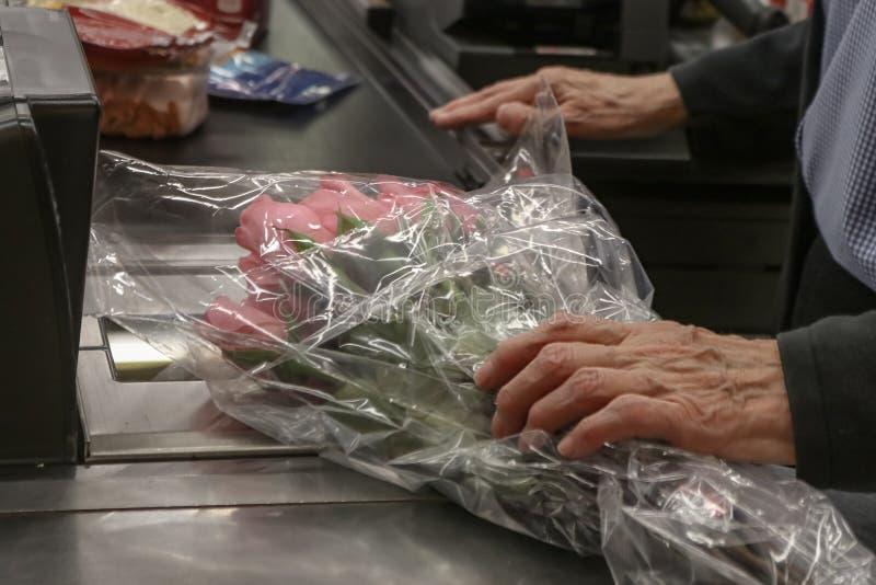 Boquet d'acquisto invecchiato anziano dell'uomo delle rose rosa al fuoco potato e selettivo del deposito - fotografia stock libera da diritti