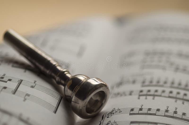Boquilla de la trompeta en el libro de partitura foto de archivo