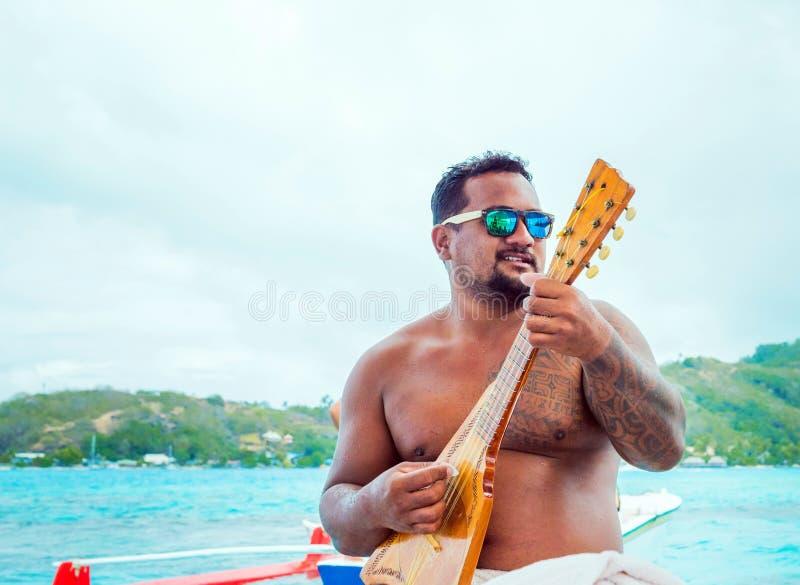 BORA BORA, FRANZÖSISCH-POLYNESIEN - 19. SEPTEMBER 2018: Ein Mann mit einer Gitarre auf dem Hintergrund der Seelandschaft Mit vorg lizenzfreies stockbild