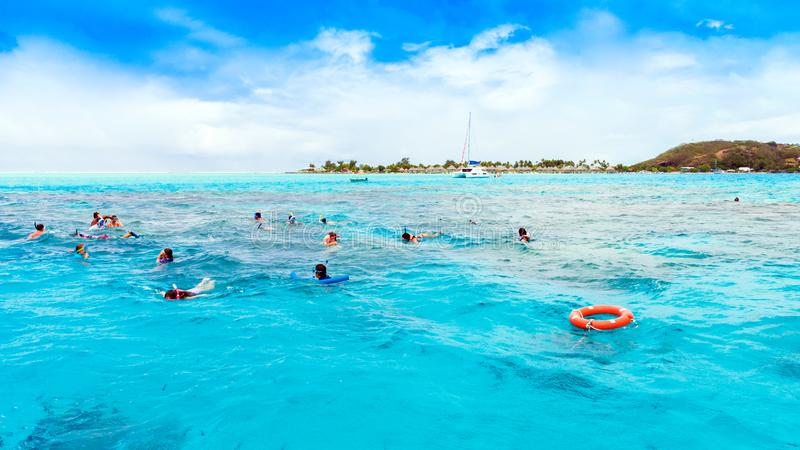 BORA BORA, FRENCH POLYNESIA - SEPTEMBER 19, 2018: People swim in the ocean with masks. Copy space for text royalty free stock image