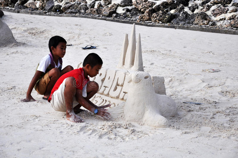 Boracay island, Philippines. August 11, 2011: two little boys are making sand tower on Boracay beach in Philippines royalty free stock image
