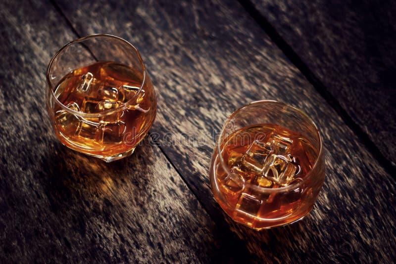 Borbón del whisky en dos vidrios en backgroudnd de madera oscuro de la tabla foto de archivo